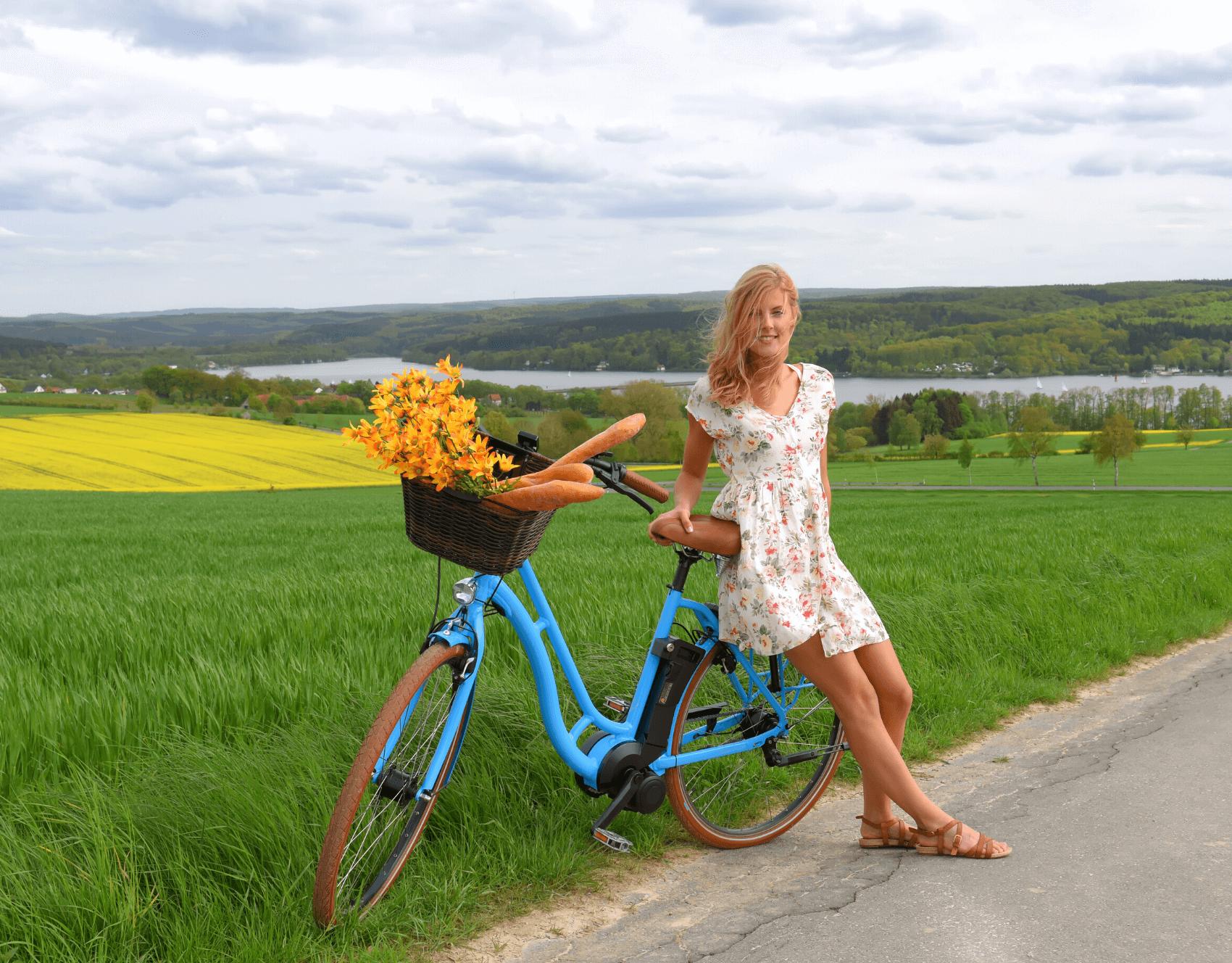 Junge Frau sitzt auf dem Gepäckträger eines blauen E-Bikes_Hotel Mama bei SRTI