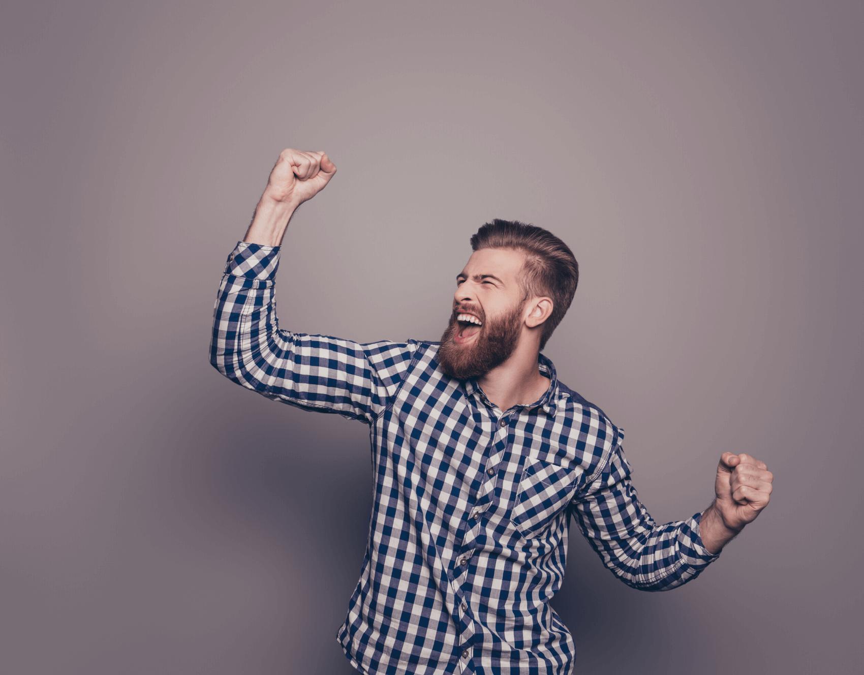 Glücklicher Mann mit gehobenen Händen schreit vor Freude